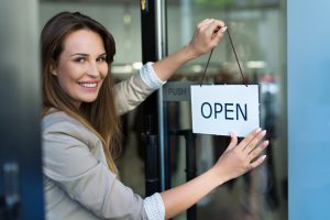 Woman hanging open sign on door