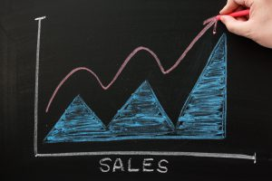 Hand drawing a red line for sales growth on a graph displayed on a blackboard.