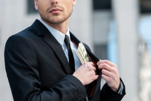 Cropped shot of a businessman placing money into his pocket
