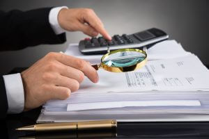 Close-up Of Businessperson Hands Checking Invoice With Magnifying Glass At Desk