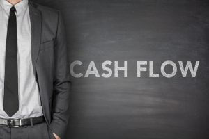Cash flow on black blackboard with businessman