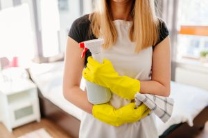 Woman wearing white apron and rubber protective yellow gloves, holding rag and spray bottle detergent. MORE FROM THIS SERIES IN MY PORTFOLIO