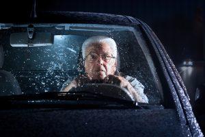 Senior driving a car in the rain