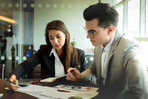 Businessman and businesswoman discuss together about there business performance.