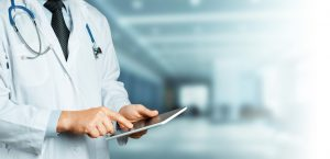 Unrecognizable male doctor in white coat with stethoscope using tablet, digital patient support system, test results and data registration
