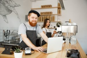 Coffee Business Concept - Young handsome bearded bartender, barista or manager working and planing in laptop at modern coffee shop.