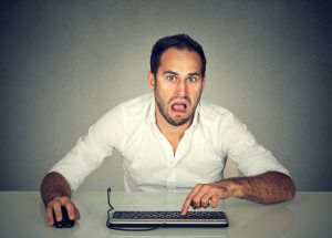 Confused upset young man working on computer