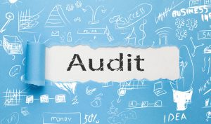 Audit text written paper on blue background
