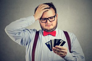 Chubby puzzled man looking at credit cards in hands looking desperate with spending money.