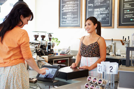 Female Owner Of Coffee Shop Serving Customer on her POS System