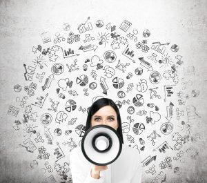 Beautiful woman with white loudspeaker, business icons behind her. Front view. Concrete background. Concept of sharing information.