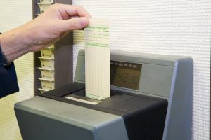 A worker is punching his time card with the automatic clock