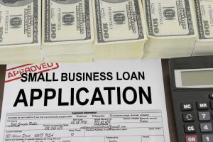 Application form  for a small business loan with stack of 100 US dollar bills and calculator
