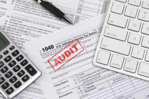 Concept image for filing federal income taxes online and being audited. Computer keyboard, calculator and pen are placed on income tax form 1040. The 'word' AUDIT is stamped on the form 1040.