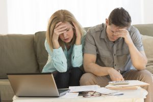 Worried mature couple calculating home finances. Man and woman are sitting on sofa, in brightly lit home.