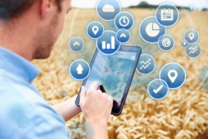 Composite Of Farmer In Field Accessing Data On Digital Tablet With Projected Icons