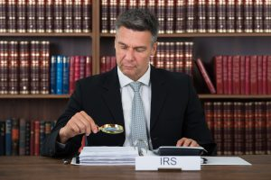 Mature male tax auditor examining documents with magnifying glass at table in office