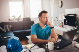 Man in blue shirt working on laptop at home office