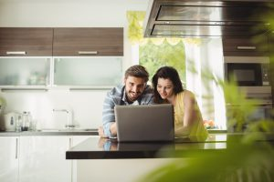 Happy couple using laptop in the kitchen