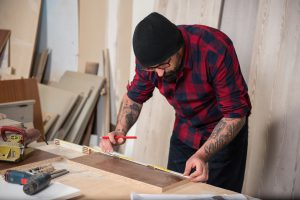Adult man with beard and tattoo working in carpenter workshop using power tools