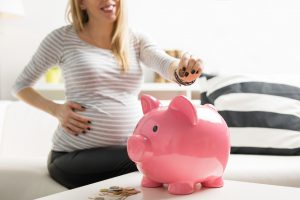 Pregnant woman putting money in piggy bank