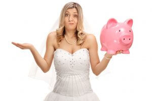Upset bride holding a piggybank and gesturing with her hand isolated on white background