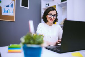 Brunette Woman In Eyeglasses Typing Morning Report At Her Desk At The Office