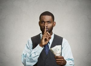Closeup portrait handsome corrupt guy businessman holding dollar bill in hand showing shhh sign finger to lips isolated grey background. Bribery concept politics, business diplomacy. Face expression