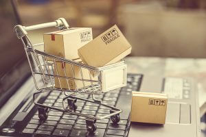 Paper boxes in a shopping cart on a laptop keyboard. Ideas about e-commerce, e-commerce or electronic commerce is a transaction of buying or selling goods or services online over the internet.