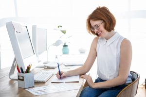 smiling hipster business woman sketching on paper at her desk