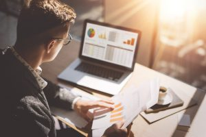 Young finance market analyst in eyeglasses working at sunny office on laptop while sitting at wooden table.Businessman analyze document in his hands.Graphs and diagramm on notebook screen.Blurred