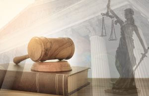 Judge gavel on law books with statue of justice and court government background. concept of law,justice, legal.