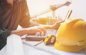 Architect engineer using laptop for working with yellow helmet, laptop and coffee cup on table.