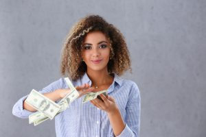 Beautiful black woman portrait. Scattering money notes dollars in fashion vows style mulatto curly hair with white locks eye view of the camera