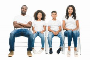 happy african american family with two children sitting on chairs isolated on white