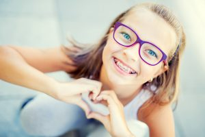 Smiling little girl with dental braces and glasses showing heart with hands.