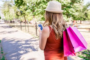 Women holding shopping bags and texting. Young woman holding colored shopping bags texting. sale, shopping, tourism and happy people concept