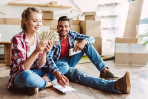 happy young couple with calculator and dollar banknotes counting money in new house