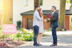 Real estate agent welcoming young visitors of open house for sale