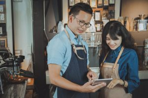 Two of asian baristas taking an order by digital tablet. Cafe restaurant service, food and drink industry concept.