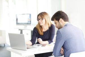 Shot of an financial advisor professional woman sitting in front of laptop and discussing with young financial assistant about business plan.