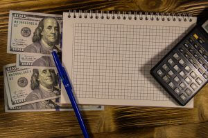 Notebook with dollars, pen and calculator on wooden desk. Financial concept
