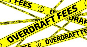 """Yellow warning tapes with inscription """"OVERDRAFT FEES"""" on the white surface. Isolated. 3D Illustration"""