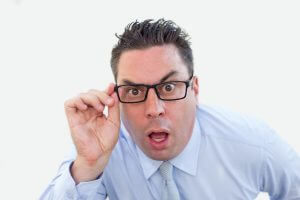 Closeup portrait of shocked middle-aged business man staring at camera through glasses. Shock concept. Isolated front view on white background.