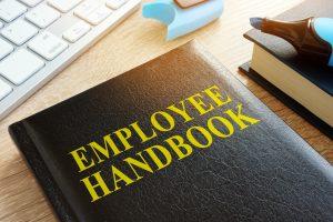 Employee handbook on a wooden desk.