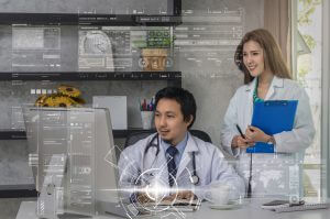 Couple of Asian doctors working with colleague which using technology computer over the technology digital virtual screen in modern office of hospital, physician technology concept