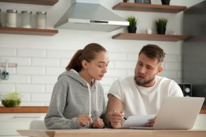 Focused young couple checking analyzing utilities bills sitting together at kitchen table, serious husband and wife reading bank loan documents with laptop, family managing finances planning expenses