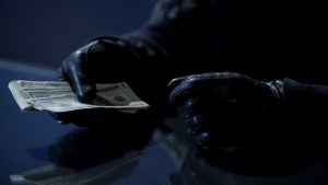 Criminal counting ransom money for kidnapping, blackmail, contract killing, stock footage