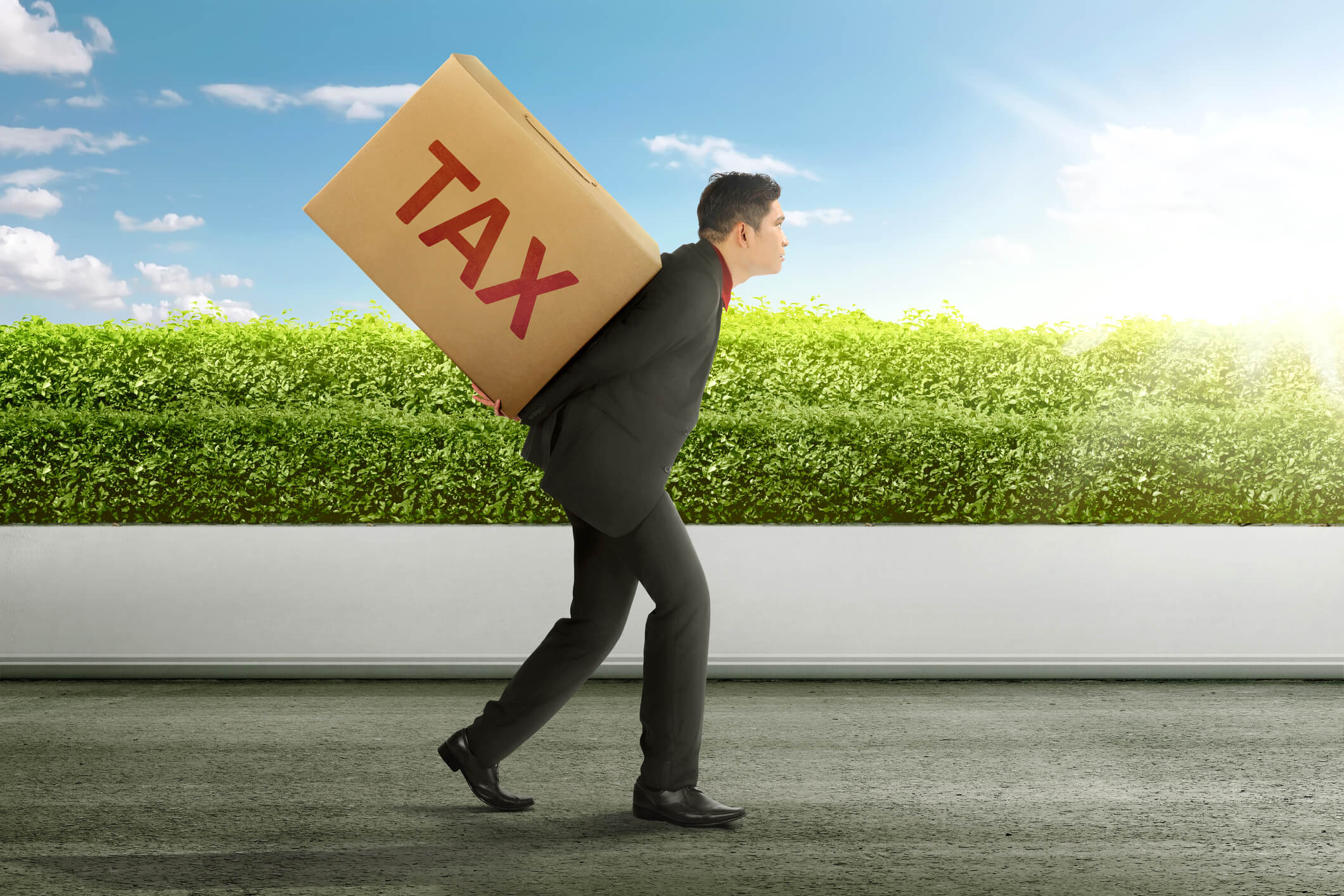 Young asian businessman carrying heavy box of TAX. Taxation concept