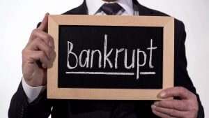 Bankrupt written on blackboard in businessman hands, loss of money and property